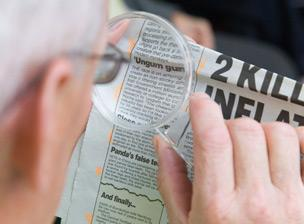 Man using magnifying glass to read